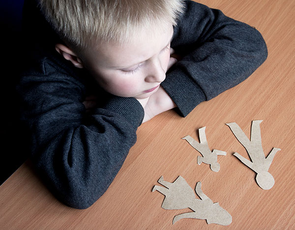 Child looking at cutouts of family members