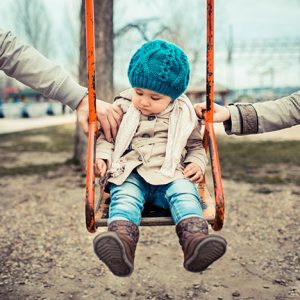 Parents on opposite sides of young child in a swing
